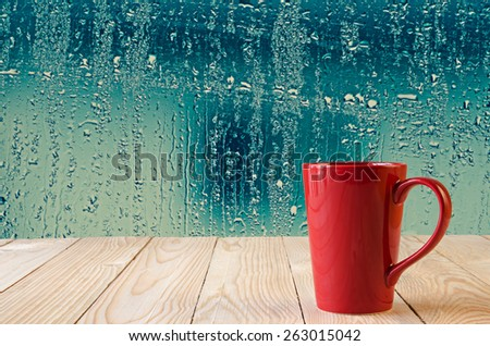 red coffee cup with natural water drops on glass window background - stock photo