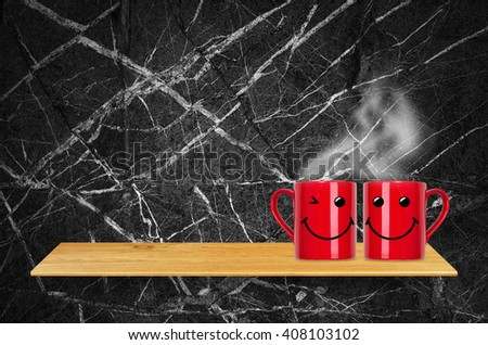 Red coffee cup with smile on bookshelf - For product display. - stock photo