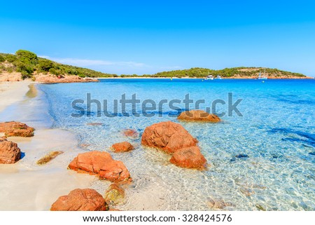 Red color rocks on Santa Giulia beach with azure sea water, Corsica island, France - stock photo