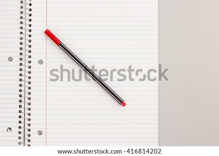 Red Colored Pen On Lined Spiral Notebook From Above - stock photo