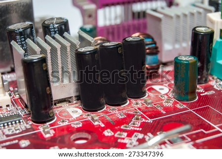 red computer motherboard with electrical components - stock photo