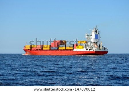 red container ship loaded with colorful cargo containers at the sea