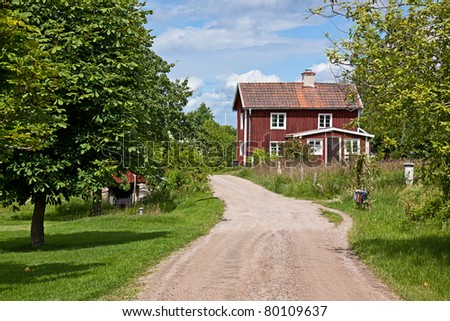 Red cottage and way through the old village. - stock photo