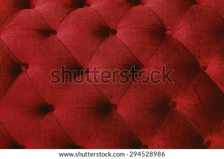 red couch background texture with sunken buttons.