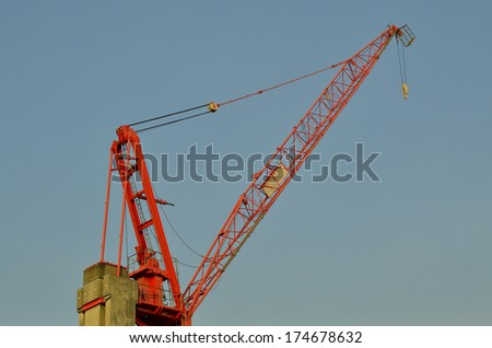 Red Crane at construction site - stock photo