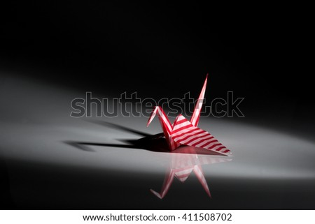 Red crane origami made from striped paper isolated on black background - stock photo