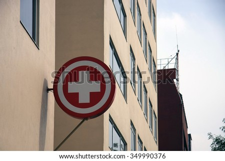 Red Cross First Aid/Medical Signage [Sign] hanging off side of a building - stock photo