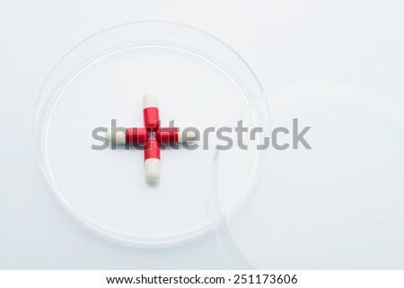 Red cross pills in petri dish - stock photo