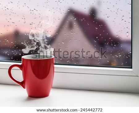 red cup of coffee on the windowsill on the background city roofs in the rain - stock photo