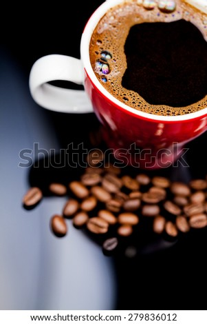Red cup of coffee with coffee beans and dark background