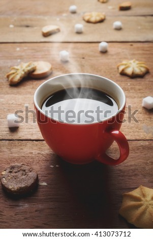 Red cup of coffee with cookies and white sugar on wood desk. Vintage tone. - stock photo