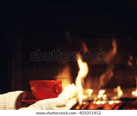 Red cup of tea or coffee in hands dressed in warm mittens near  fireplace. Winter and Christmas holiday concept. Photo with retro filter effect. - stock photo
