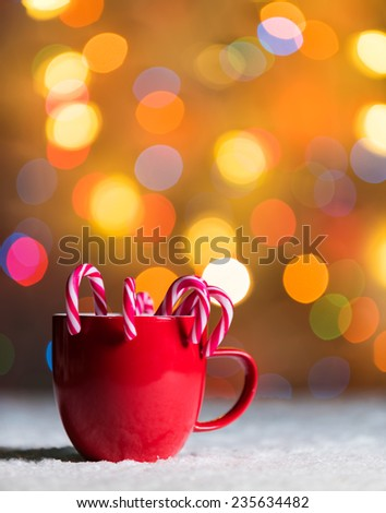 Red cup, red mug with candy canes in snow with defocussed fairy lights, bokeh in the background, Festive Christmas background with copyspace - stock photo