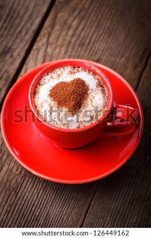 Red cup with cappuccino and heart decoration over foam. Valentine's day cup. Love concept - stock photo