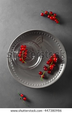 Red currant berries on plate on grey background, top view - stock photo