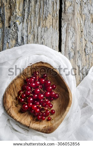 Red currant in the wooden bowl - stock photo