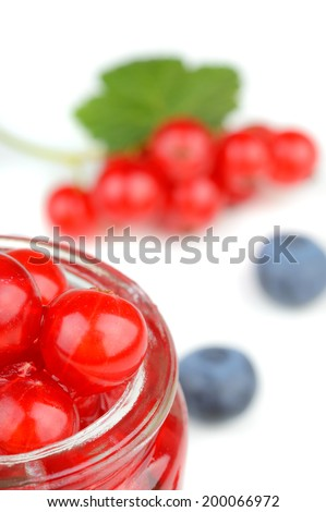 Red currants in a small jar with assorted berries around isolated on white background - stock photo
