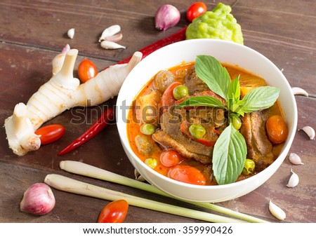 Red curry with roast duck in chalice and ingredient delicious, on old wooden table / Still life - stock photo