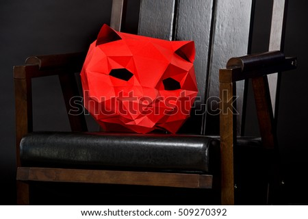 Red 3D mask of a cat on chair