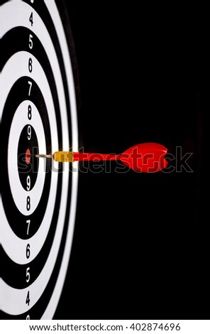 Red dart arrow hitting in the target center of dartboard with black background - stock photo