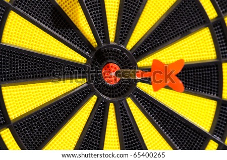 Red dart arrow in bulls eye in dart game board - stock photo