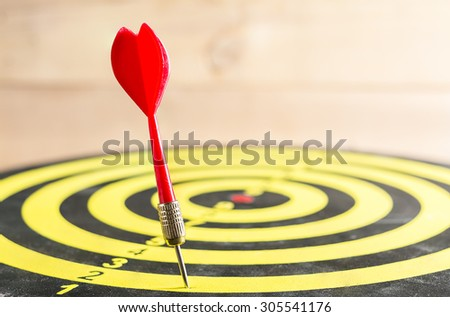 Red dart arrow missed in the target center of dartboard - stock photo