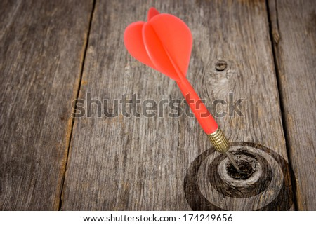 Red dart hitting target on a wooden planks - stock photo