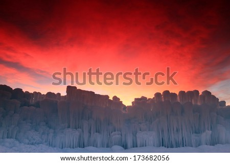 Red dawn sky above frozen ice formations, Utah, USA. - stock photo