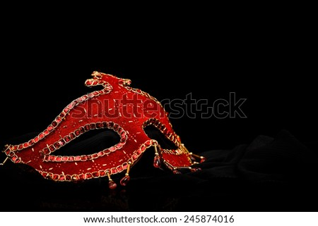 Red decorated carnival mask on black background - stock photo
