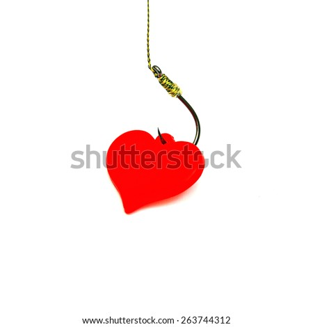 Red decorative plastic heart on the black fishing hook on the white background, close up - stock photo