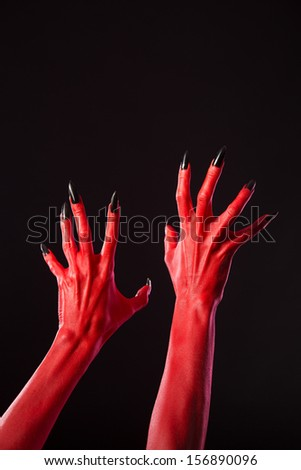 Red devil hands with sharp black nails, Halloween theme, studio shot on black background  - stock photo