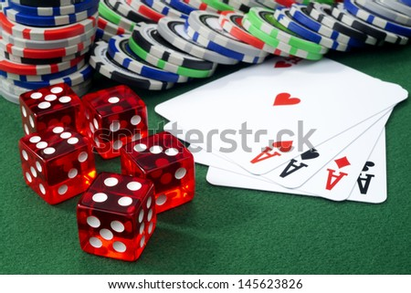 Red dice, four aces and chips on a green felt. Selective focus  - stock photo