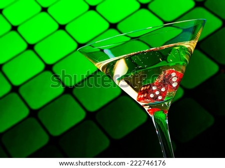 red dice in the cocktail glass on blur green background - stock photo
