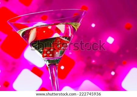 red dice in the cocktail glass on blur pink background with space for text - stock photo