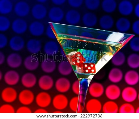 red dice in the cocktail glass on colorful gradient bokeh background - stock photo