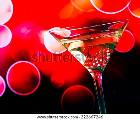 red dice in the cocktail glass on red bokeh background - stock photo