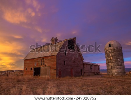 Red dilapidated barn and silo with mountain wave cloud at sunrise - stock photo