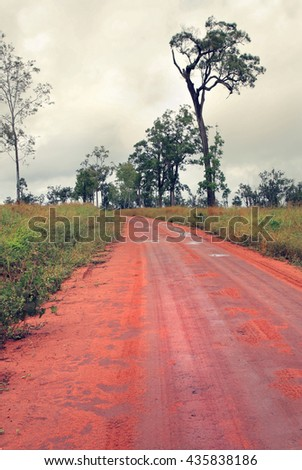 red dirt road in Australia on overcast  and rainy day - stock photo
