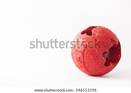 Red dog ball that has been chewed on white background