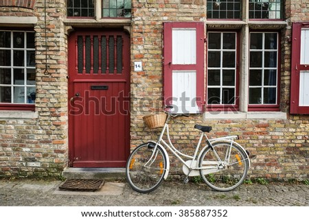 Red door, bicycle and window of old house in european city. Bruges (Brugge), Belgium, Europe. Colorful house in Old Town with a bike near the picturesque entrance.   - stock photo