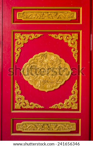 Red door with dragon statue in Thai-Chinese temple.