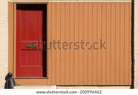 red door with orange wall along the street - stock photo
