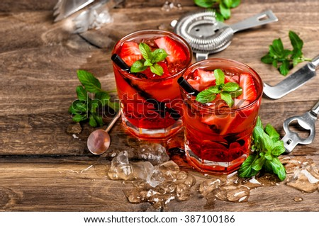 Red drink with ice, mint leaves and strawberry. Cocktail making bar tools - stock photo