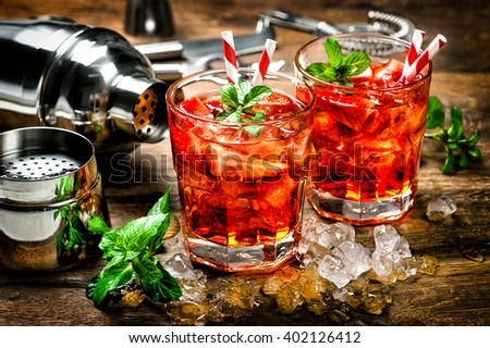 Red drink with strawberry, mint leaves, ice. Cocktail making bar accessories. Vintage style toned picture - stock photo