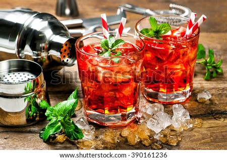 Red drink with strawberry, mint leaves, ice. Cocktail with campari, aperol, gin, liquor, juice, soda water - stock photo