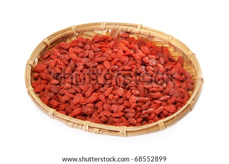 Red dry goji berries in bamboo basket on a  white background