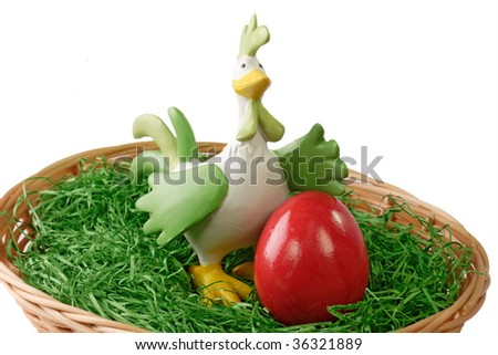 Red easter egg and a cock in a basket on bright background
