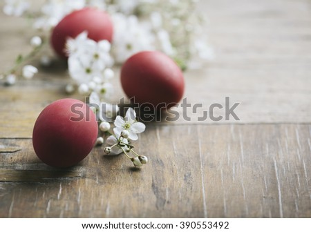 Red easter eggs and spring blossom on rustic wooden table - stock photo