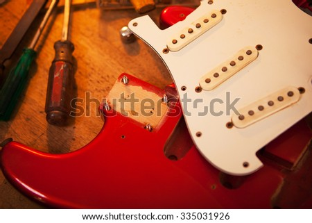 Red electric guitar on guitar repair desk or in a repair work bench. Neck and pickguard detached. Solid body guitar, red metallic color. Shallow depth of field. - stock photo