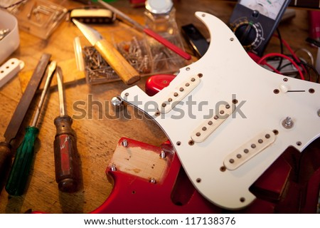 Red electric guitar on guitar repair desk or in a  repair work shop. Neck and pickguard detached. Double cutaway solid body guitar, red metallic color. Shallow depth of field. - stock photo